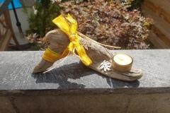 Schwemmholz als Kerzenständer mit gelber Schleife